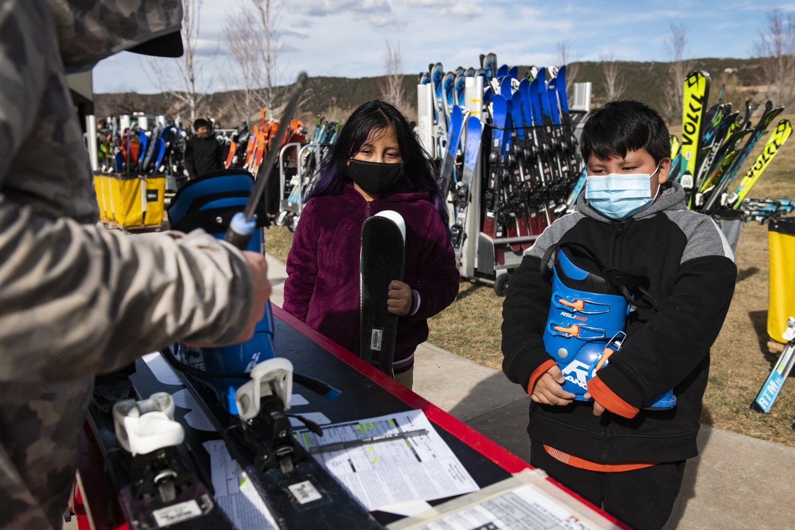 Gorsuch ski technician Alex Guerin, left, helps Geraldine Moron, 9, left, and her brother Dylan Maron, 7, with their first pair of skis at the Gorsuch and AVSC equipment day in El Jebel on Wednesday, Nov. 18, 2020. This will be both childrens first season skiing and Geraldine said shes excited, but a little nervous. (Kelsey Brunner/The Aspen Times)