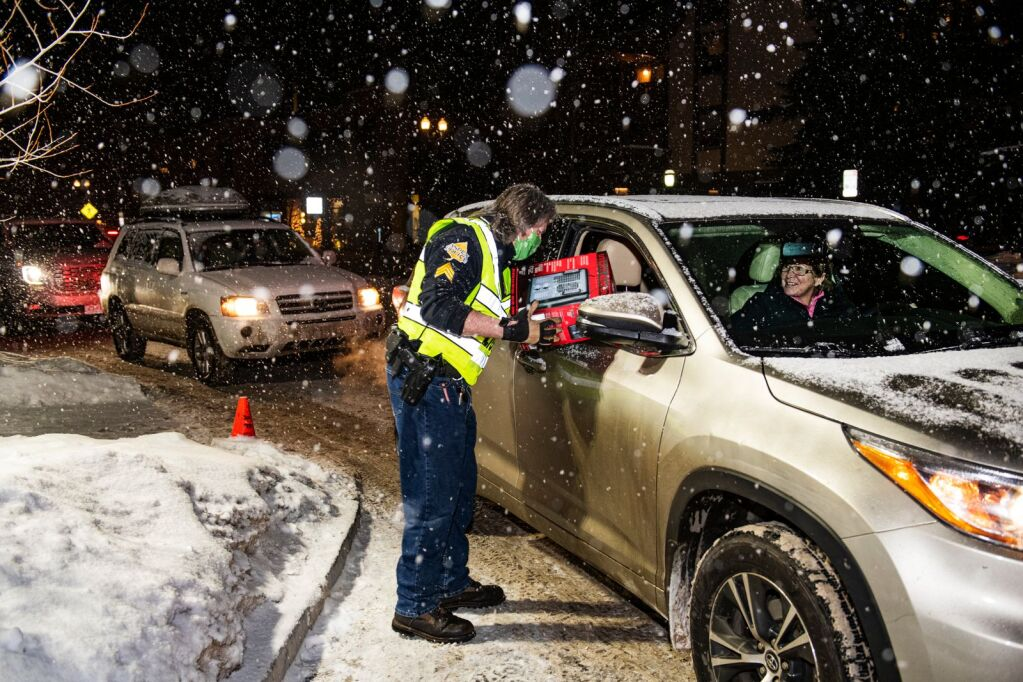 Sergeant Terry Leitch provided a heater to an Aspen resident outside the Aspen Police Station on Monday, December 28, 2020. More than an hour later, due to the gas interruption in Aspen area, all the heaters were heated by the residents, but there was no heating. People waited in line in their cars and walked up to pick up the heaters. Aspen Police Department is expected to deliver another batch of heaters.  (Kelsey Bruner/Aspen Times)
