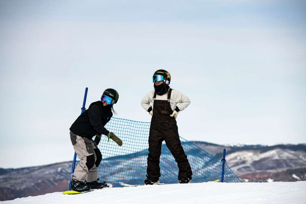 Snowboarders Kokomo Murase, left, and Reira Iwabuchi share a moment under the second jump on the slopestyle course during a practice for the 2021 X Games at Buttermilk on Thursday, Jan. 28, 2021. (Kelsey Brunner/The Aspen Times)