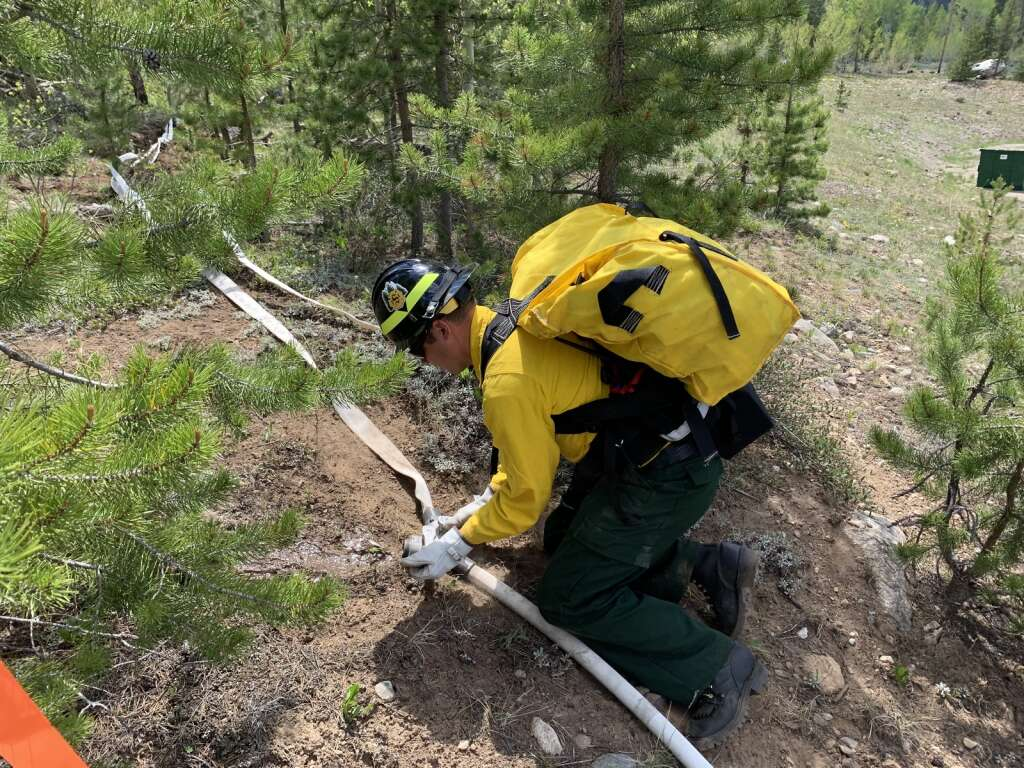 A firefighter unwraps a hose along the scratch line during a wildland firefighting exercise Tuesday, June 8, near County Commons. | Photo by Sawyer D'Argonne / sdargonne@summitdaily.com