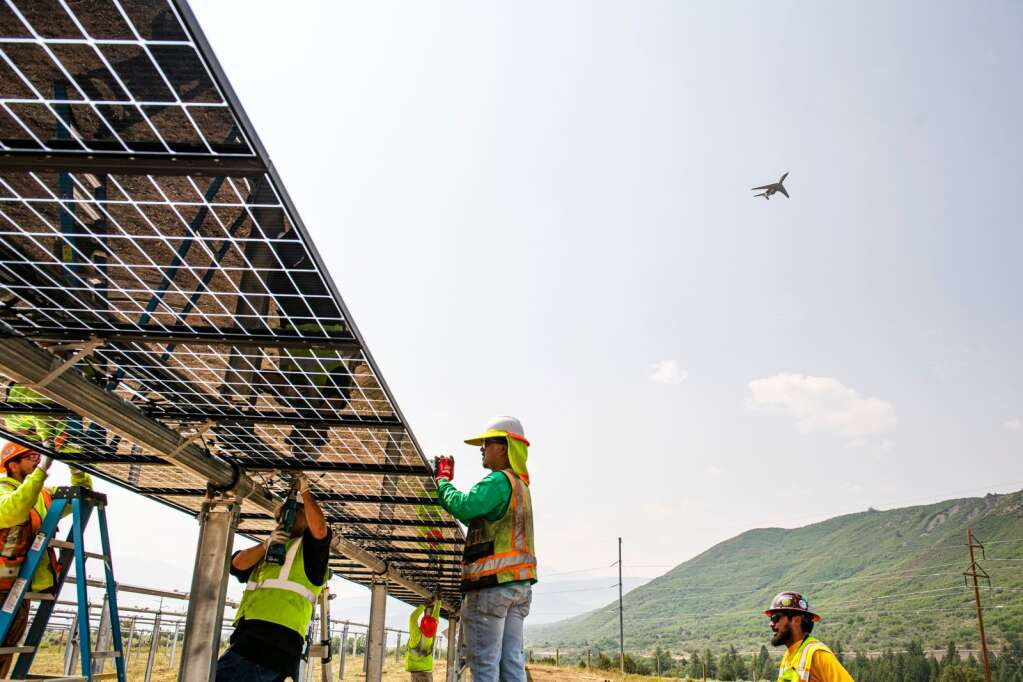"""A plane flies over the 35-acre solar farm while the """"golden row,"""" or first row, of solar panels is installed  Tuesday, August 10 outside of Woody Creek. The modules will continue to be installed through the month with expectations that energy will be harnessed from the site starting in October. (Kelsey Brunner/The Aspen Times)"""