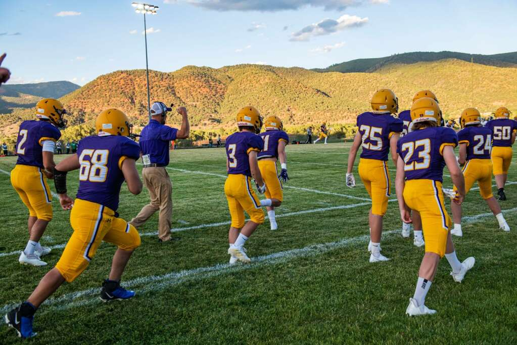 Longhorns coach Aaron Munch and the team run down the sidelines after scoring a touchdown in the first few minutes of the season opener against Woodland Park at Basalt High School on Friday, Aug. 27, 2021. (Kelsey Brunner/The Aspen Times)