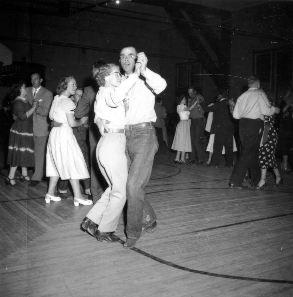 One b/w photograph of a cowboy dance held in the Armory Hall (City Hall) in Aspen on August 14, 1949.  Couples are dancing on a wooden floor.Aspen Historical Society, Berko Collection