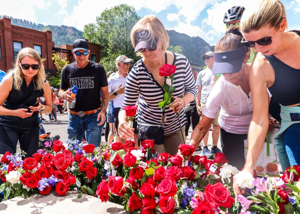 People grab roses in front of the Aspen Fire Protection District building in downtown Aspen after the September 11, 2001 memorial ceremony in New York City on Saturday, September 11, 2021.  Photo by Austin Colbert / The Aspen Times.