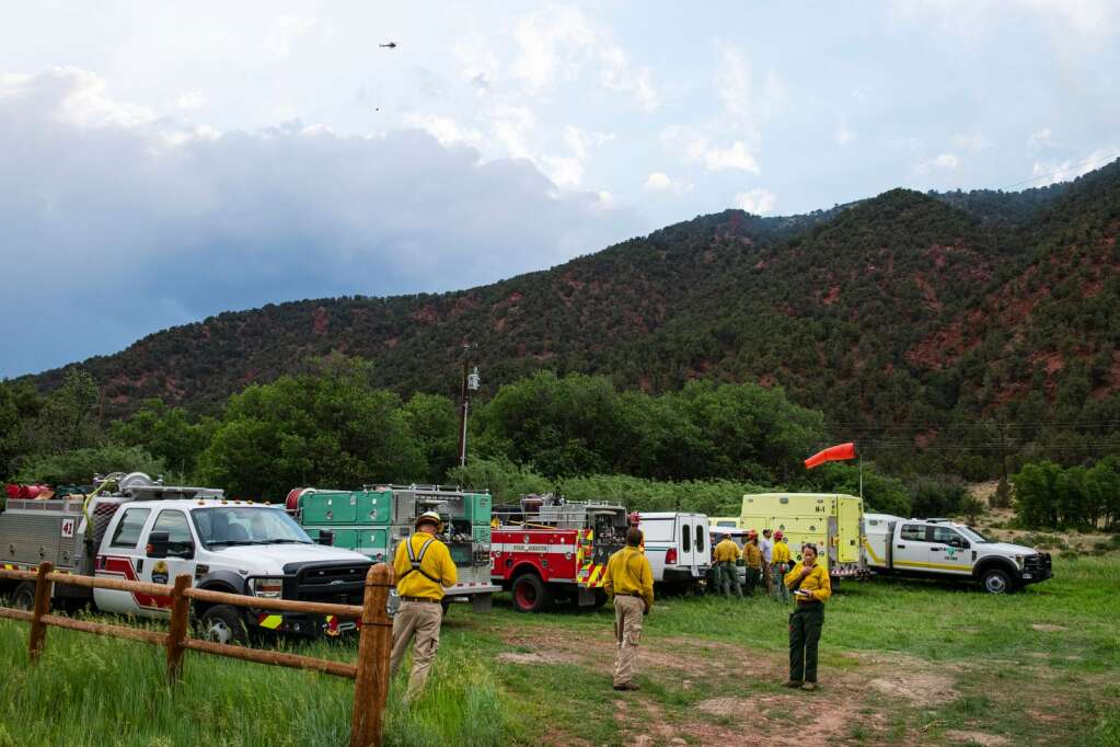 Wildland firefighters standby as a helicopter brings a load of water to drop on a fire that broke out from a lightning strike near Lower River Road in Old Snowmass on Friday, June 18, 2021. (Kelsey Brunner/The Aspen Times)