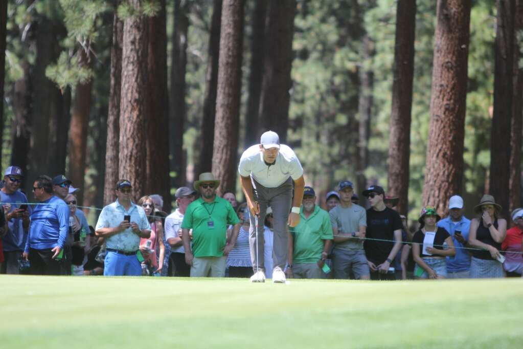 Tony Romo looks for his putting line.