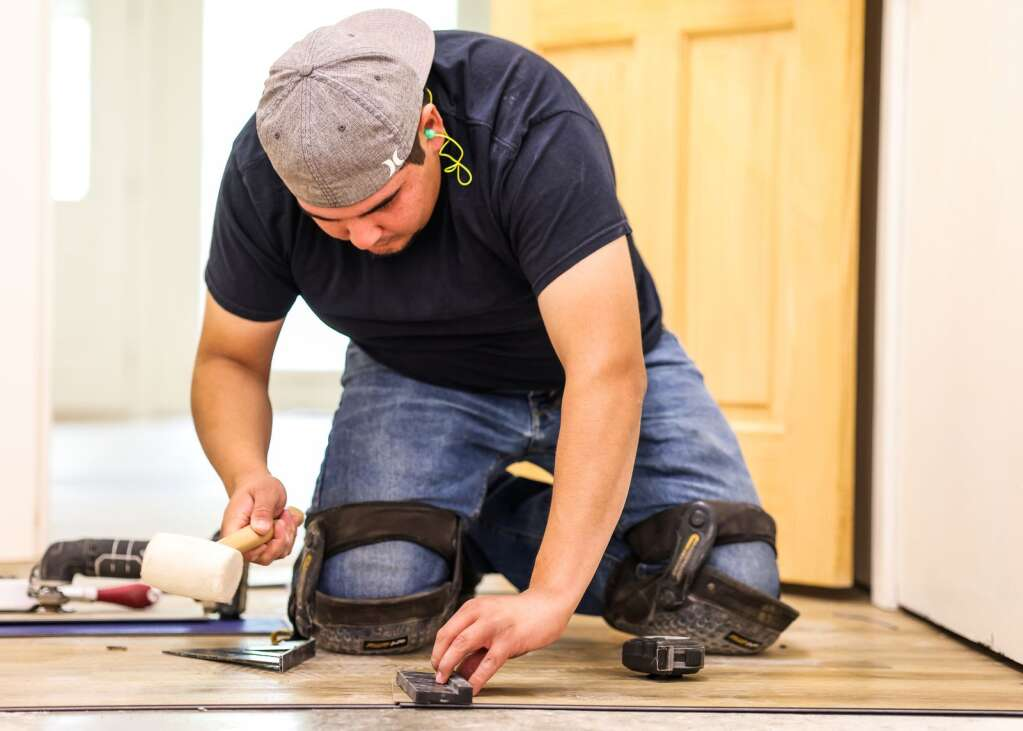 Chuy Perales installs flooring in the main lodge at the Aspen Camp of the Deaf and Hard of Hearing in Old Snowmass on Sunday, May 23, 2021. | Austin Colbert/The Snowmass Sun