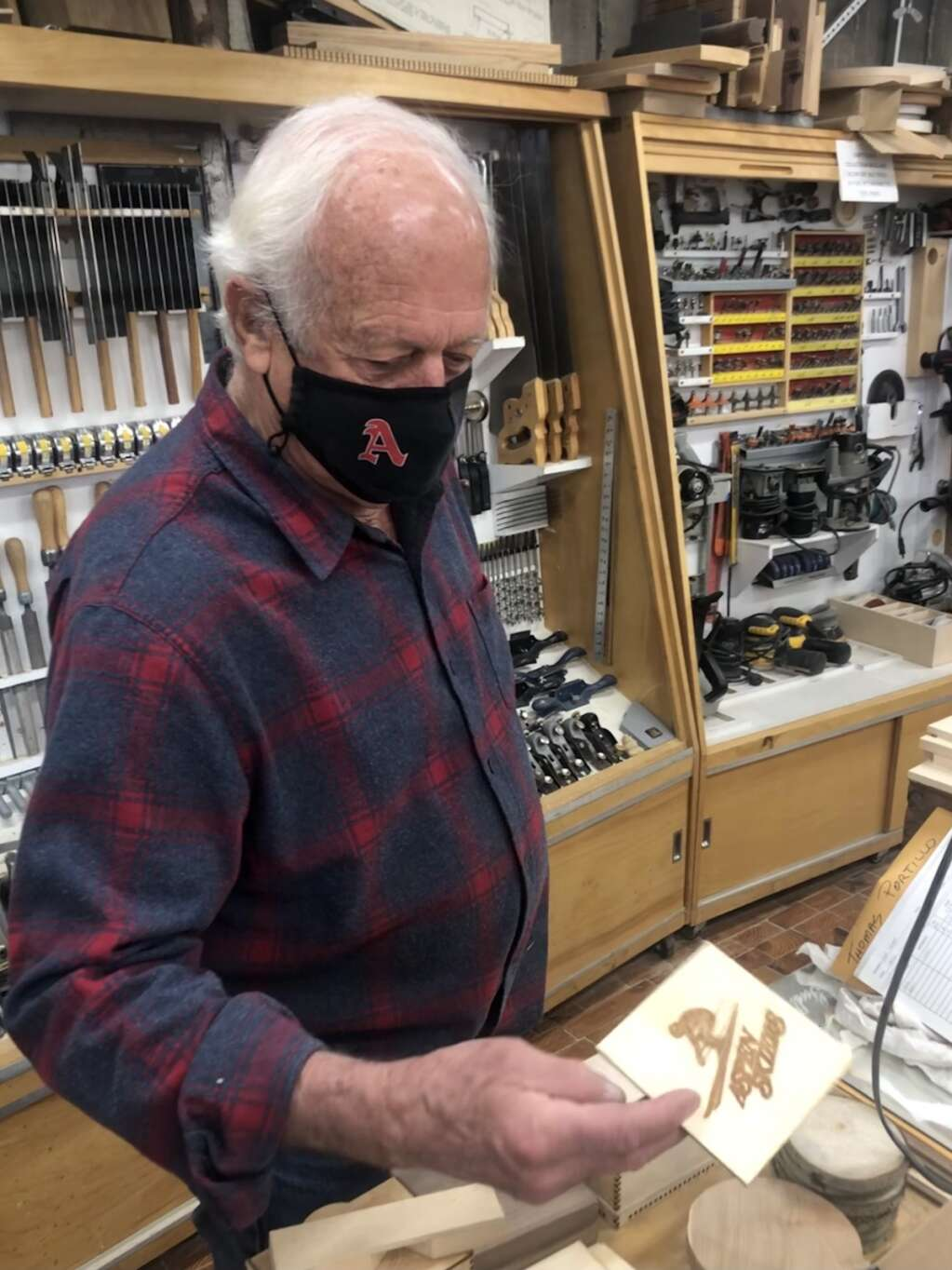John Fisher holds up an Aspen Skiers coaster in his workshop at Aspen High School on March 22, 2021. | Kaya Williams/The Aspen Times