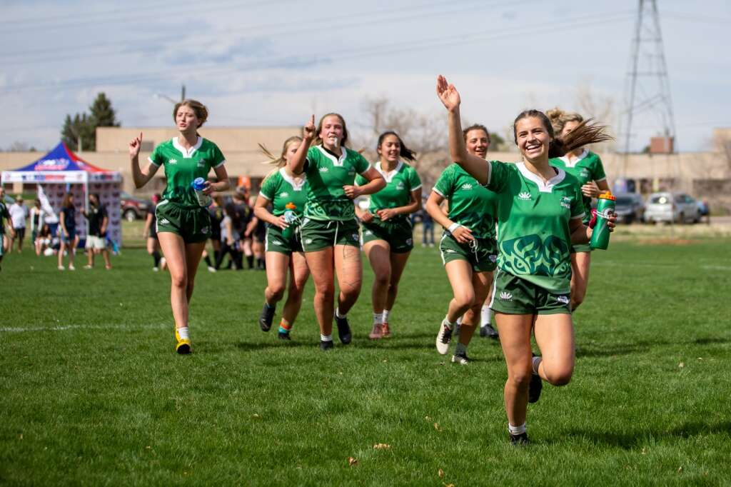 The Summit Tigers run off the field at Cook Park in Denver, Colo., after winning their final game against Monarch at the high school rugby state championships on Saturday, May 1, 2021. As the Tigers won their first game, tied the second, and claimed victory in the third, the Summit High girls rugby team clinched their 13th-straight state championship title. | Photo by Liz Copan  /Studio Copan