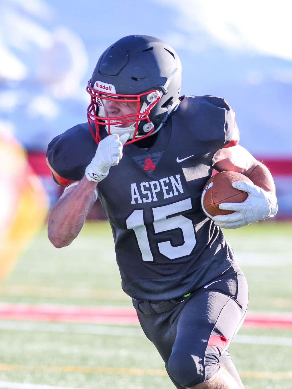Aspen High School football player Judd Gurtman runs with the ball against Montezuma-Cortez on Friday, April 2, 2021, on the AHS turf. (Photo by Austin Colbert/The Aspen Times)