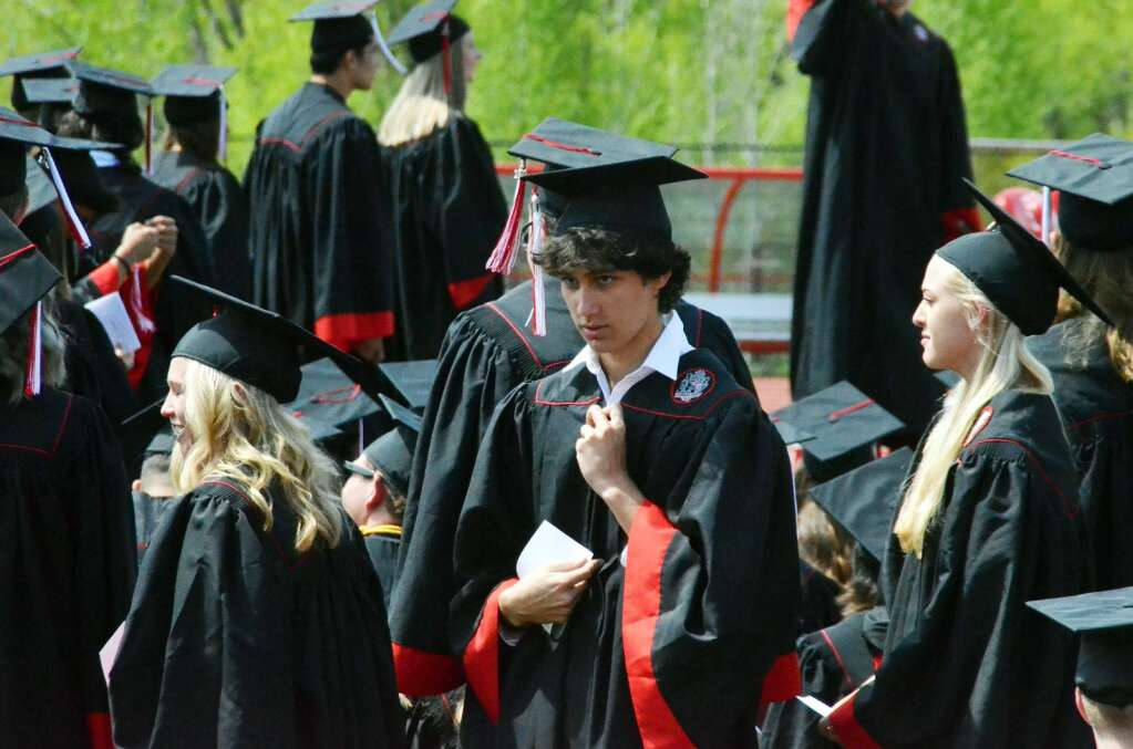 Jonnathan Simoes fixes his collar as he stands in line to head onto the stage. (Photo by Bryce Martin)