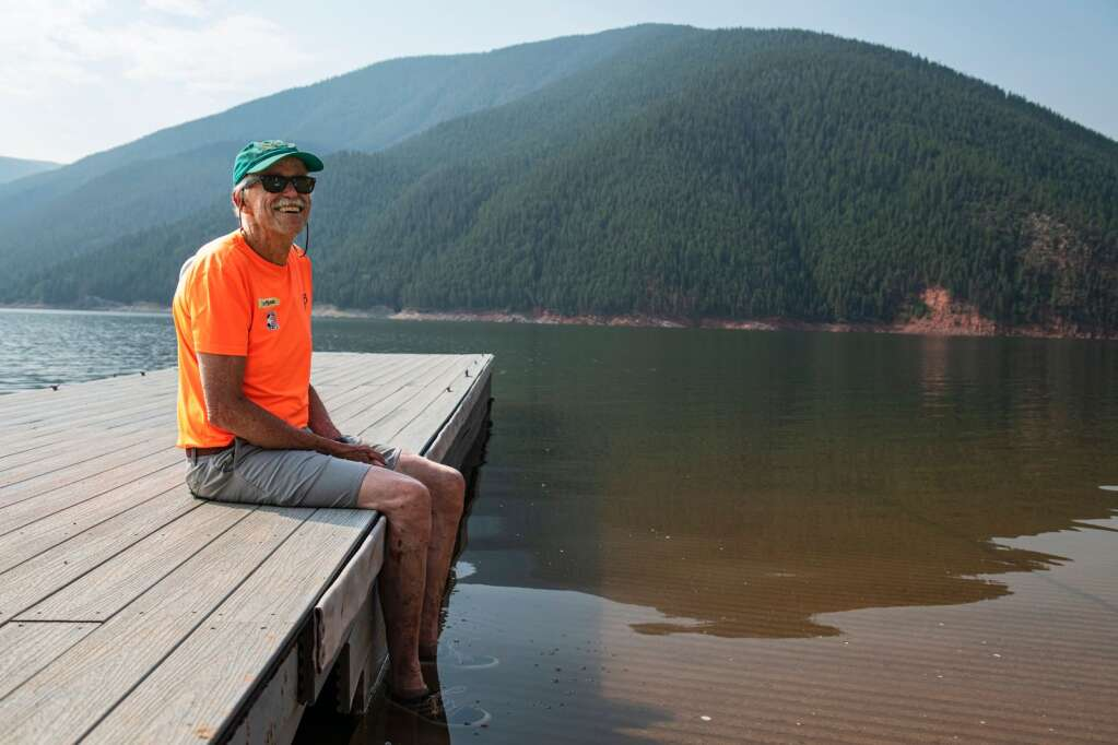 Ruedi Rowers Boat Club member Steve Prudden dangles his feet into the water while sitting on a dock at the boat ramp of Ruedi Reservoir on Tuesday, July 13, 2021. (Kelsey Brunner/The Aspen Times)