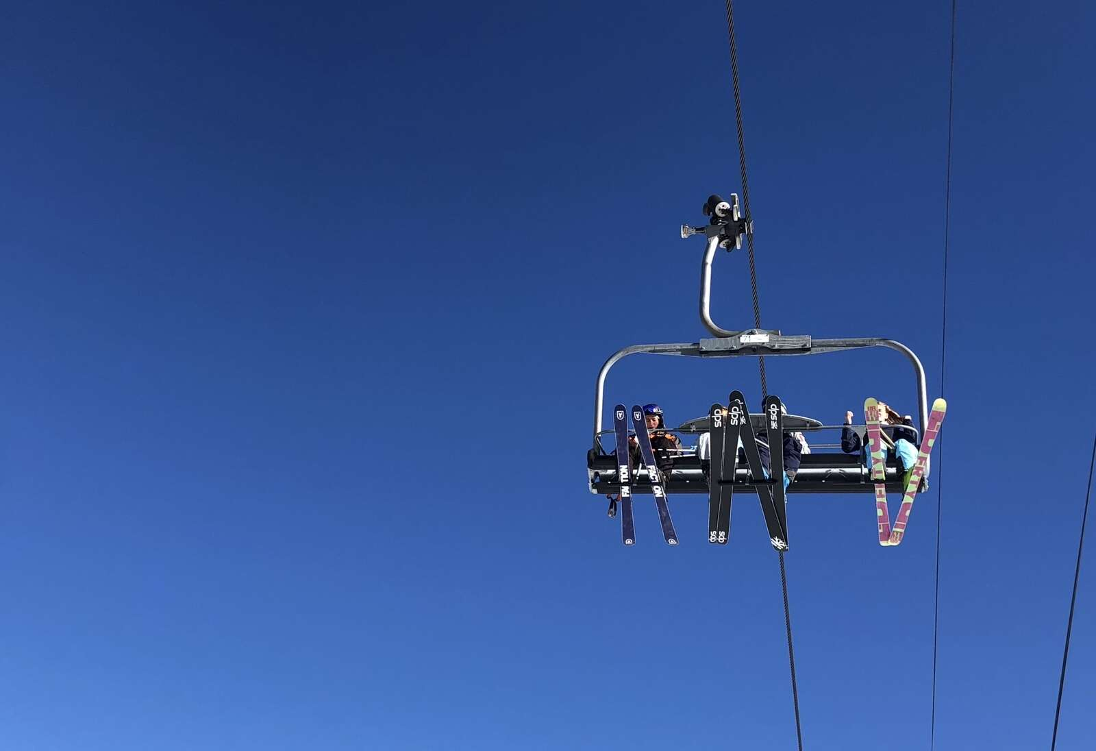 A group of four skiers ride the Village Express chairlift on opening day at Snowmass. Per the resort's COVID-19 lift policy,
