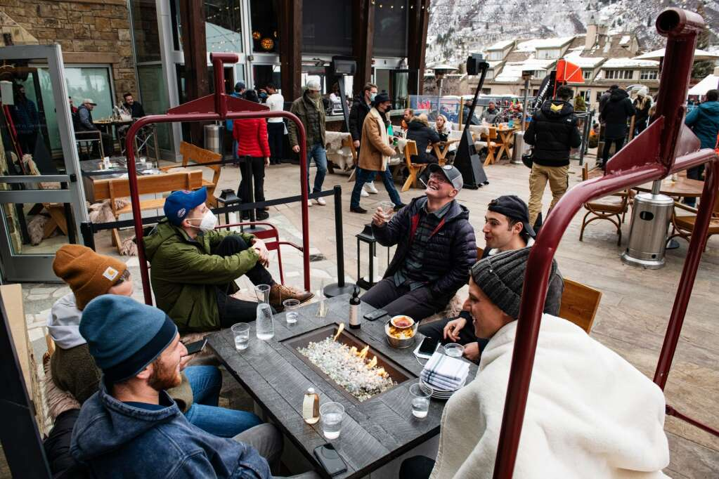 People enjoy apres on the patio of Dante at The Snow Lodge at the base of Aspen Mountain on Friday, Jan. 22, 2021. (Kelsey Brunner/The Aspen Times)