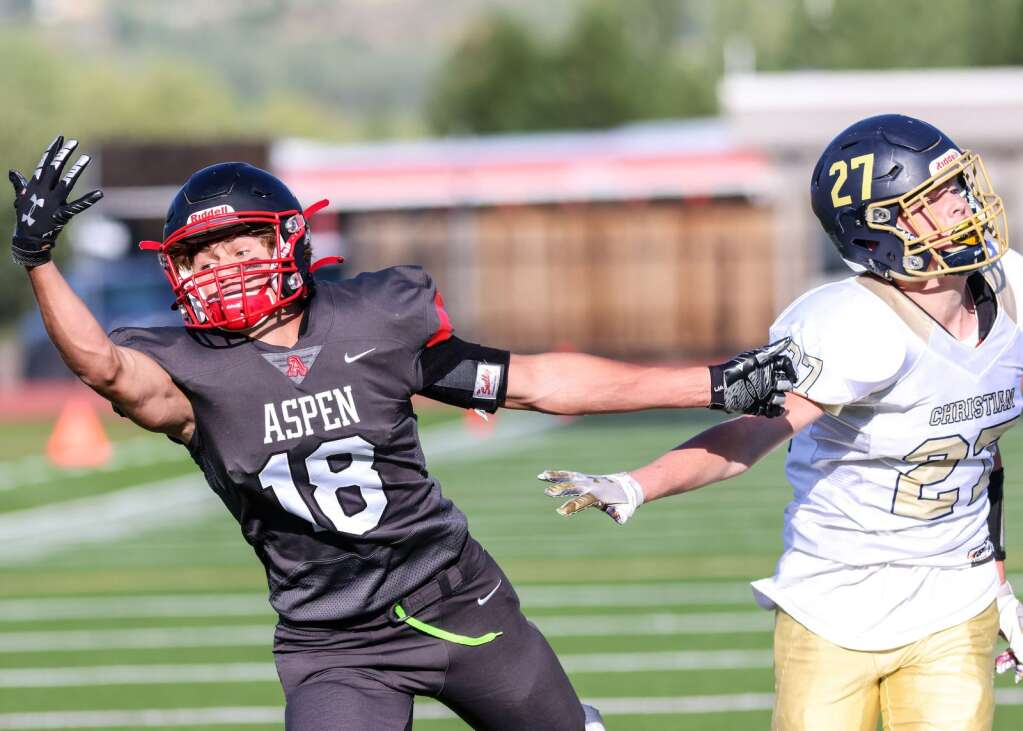 Aspen High School's Aiden Flynn, left, attempts to catch a pass as the football team hosts Colorado Springs Christian on Friday, Aug. 27, 2021, on the AHS turf. | Photo by Austin Colbert/The Aspen Times