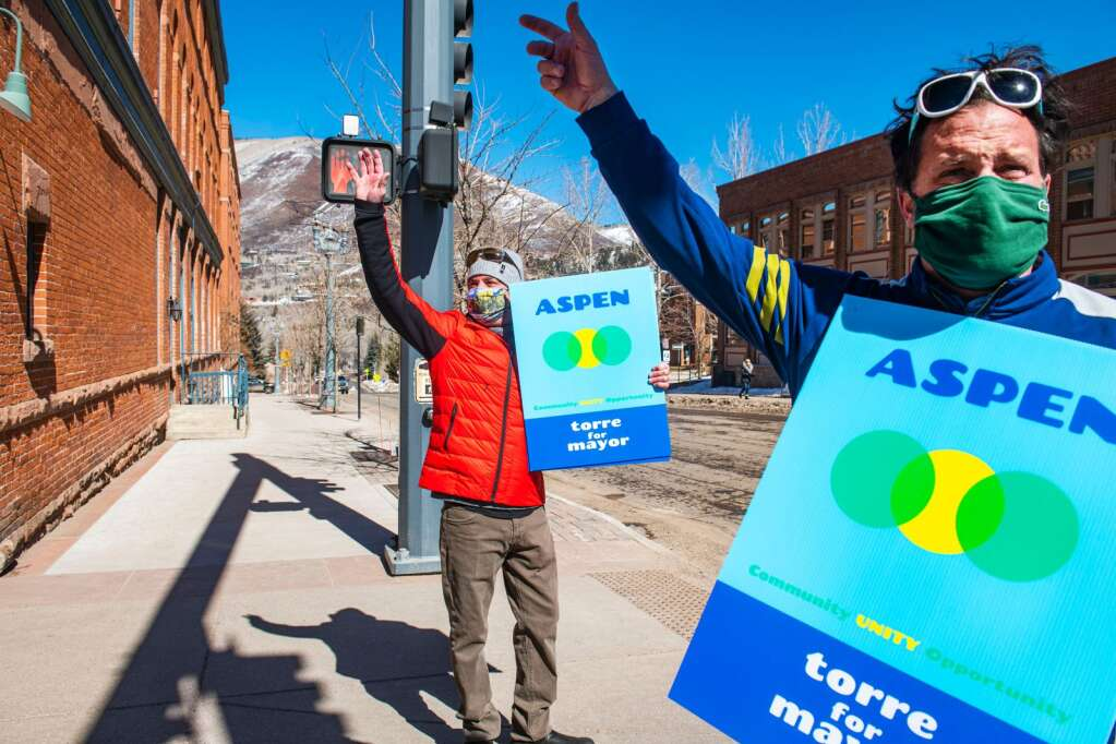Aspen Mayor Torre, left, waves at passing cars with longtime friend Shane Smith while campaigning for Tuesday's municipal election for another two-year term outside of Hotel Jerome on March 2, 2021. (Kelsey Brunner/The Aspen Times)