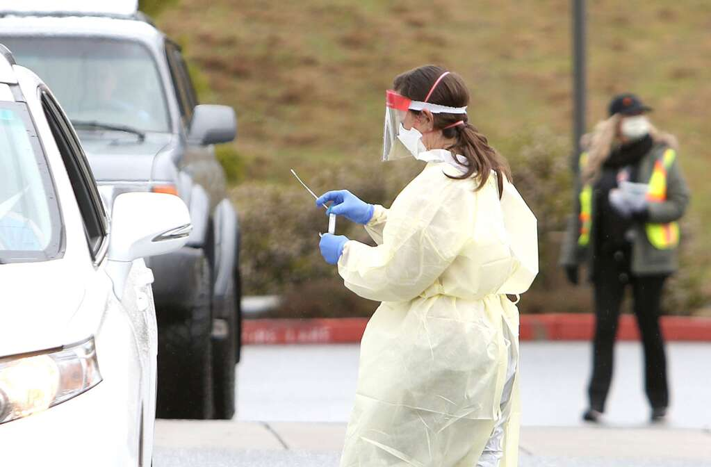 A Sierra Nevada Memorial Hospital nurse in full protective gear, places a potential COVID-19 sample into a vial to be tested during  a March 18 drive-thru coronavirus testing outside of the hospital. | Photo: Elias Funez
