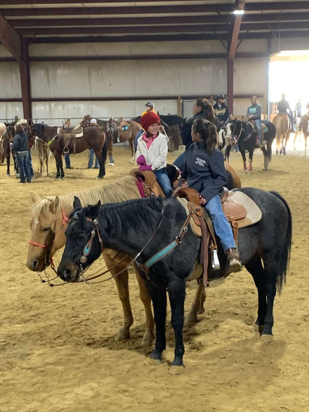 Little cowgirls chat during an equine event at the Kluz facility.