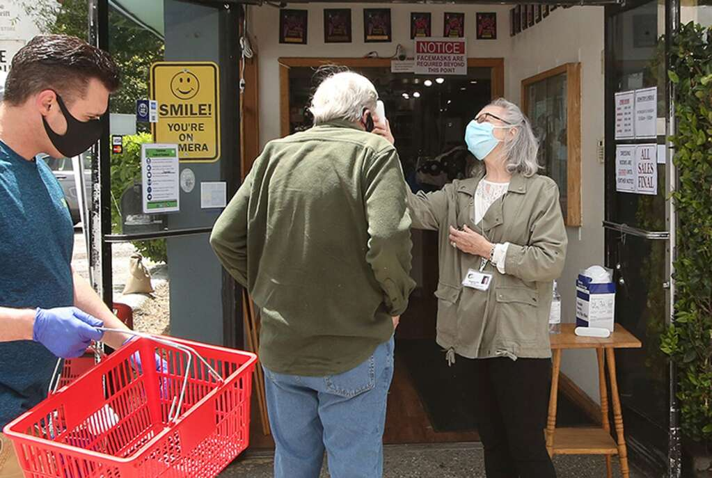 Aside from being required to wear masks, Hospice of the Foothills Gift and Thrift store employees check everyone's temperature and ask them to use a provided hand sanitizer upon entering after the store re-opened May 20. | Photo: Elias Funez