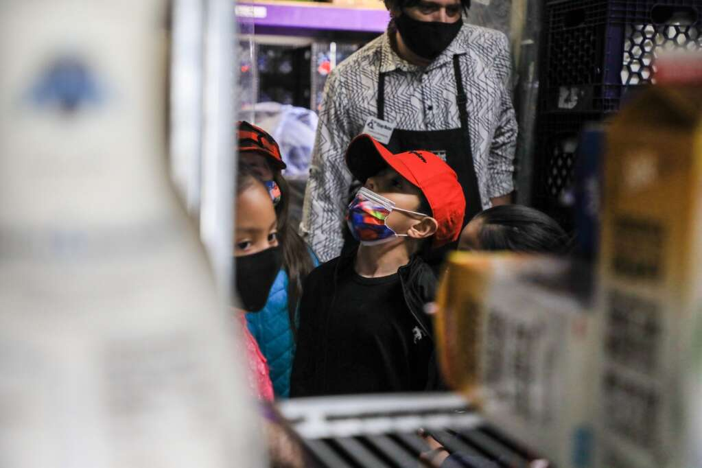 First-grader Damian Rosales Rocha checks out the cooler at Village Market Monday in Edwards. The students got a tour of the store and learned how they try to be environmentally sustainable.