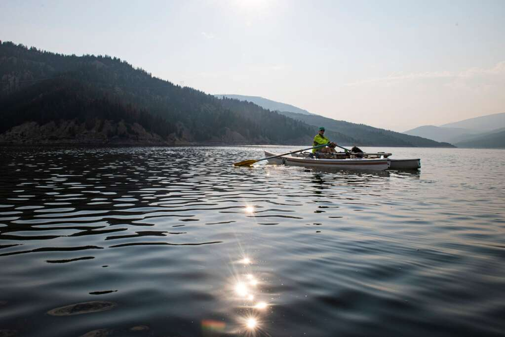 Jack Rafferty rows across a smooth Ruedi Reservoir in the early morning on Tuesday, July 13, 2021. (Kelsey Brunner/The Aspen Times)