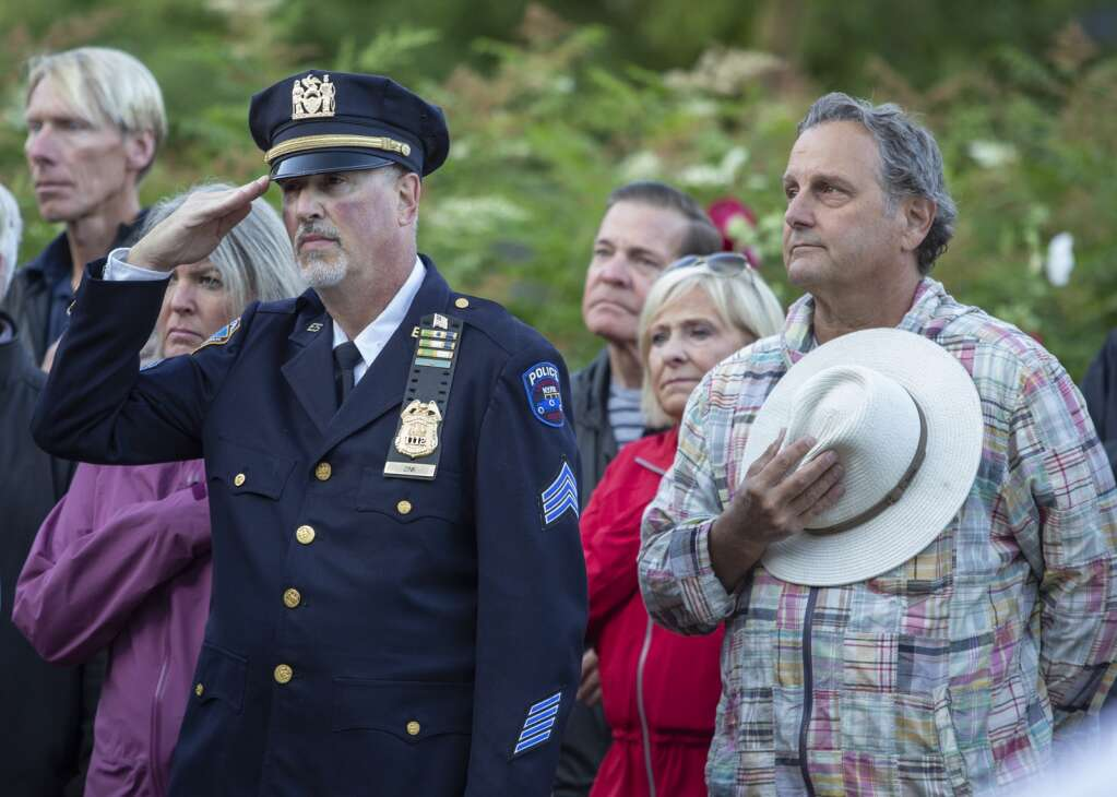 Scott Zink, left, salutes the American flag as it is risen to half mast in front of the Miners Hospital in City Park on Saturday morning during a ceremony marking the 20th anniversary of the Sept. 11 terrorist attacks. (Tanzi Propst/Park Record)