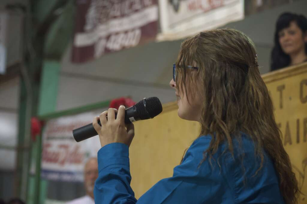 Kiki Bohrer sings the National Anthem at the Moffat County Fair livestock auction Saturday evening. | Cuyler Meade / Craig Press