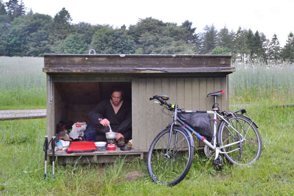 Tait cooking dinner in a bike touring shelter, Denmark.