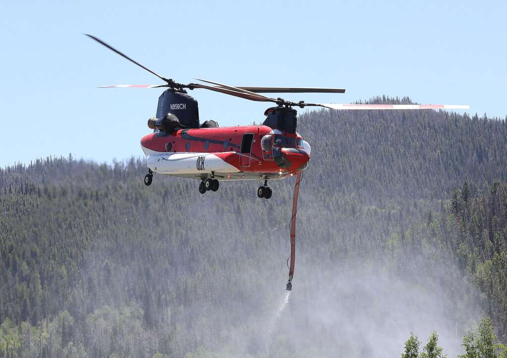 A Chinook firefighting helicopter draws water from a pond on a ranch near the Muddy Slide Fire in South Routt County just east of Yampa on Monday. The helicopter, which has the capacity to haul 1,200 gallons of water per trip, was being used to fight the fire and made a trip to the blaze every six to seven minutes. | John F. Russell/Steamboat Pilot & Today