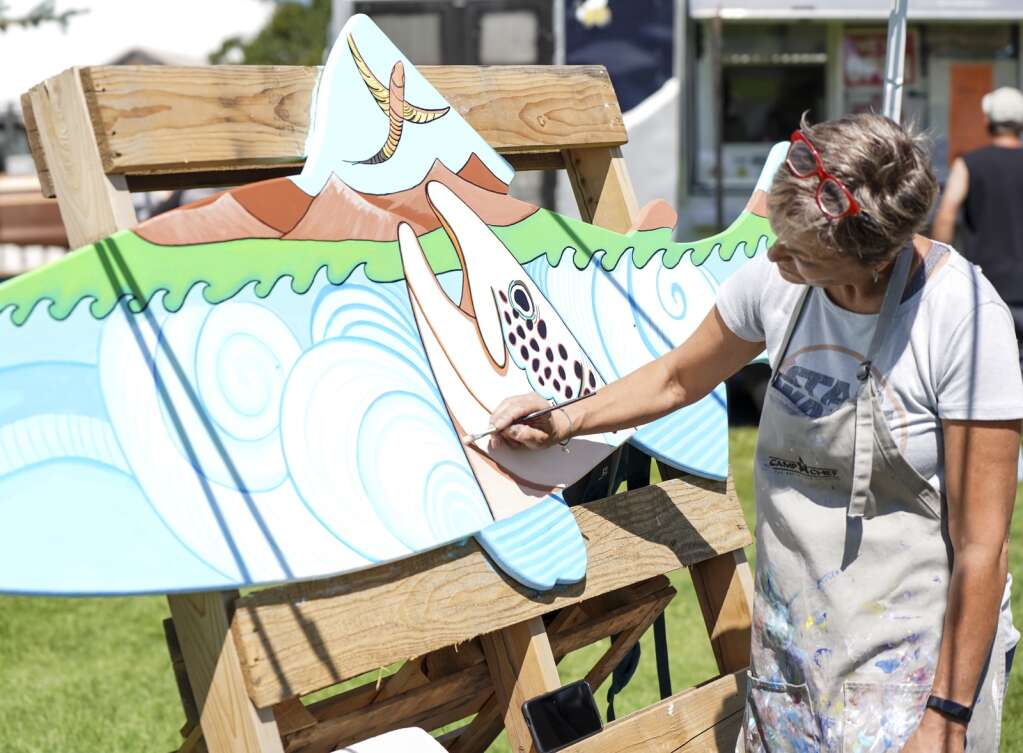 Artist Kendal Flynn paints a fish panel on Saturday, Sept. 4, 2021, at the Art in the Park festival in Granby.   Eli Pace / Sky-Hi News