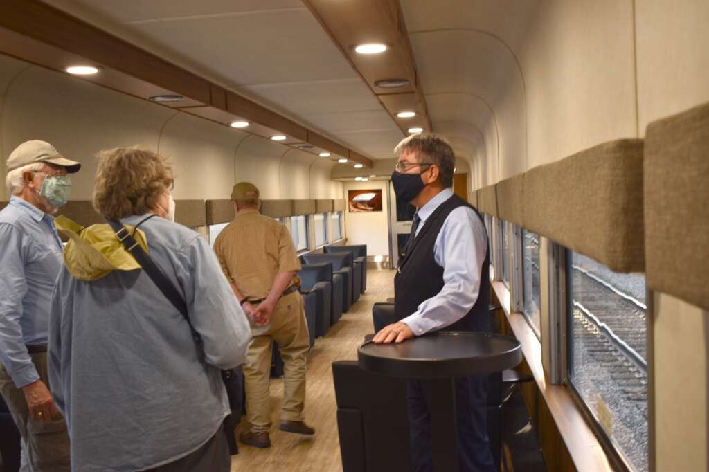 Host Michael Hannifin, right, gives a mini tour of the lounge car that's part of the luxury Rocky Mountaineer train, as it made its maiden stopover in Glenwood Springs Sunday night.