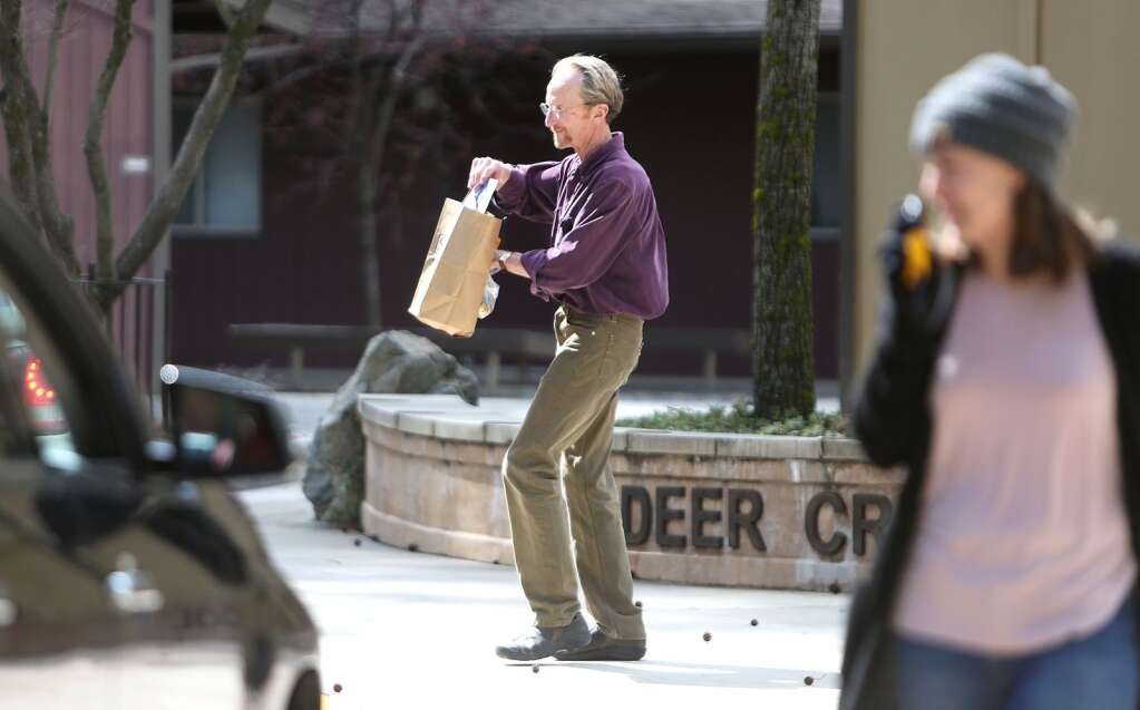 Deer Creek Elementary School first grade teacher John Carr hands an eight day supply of education for students to take home as Nevada City School District began their rollout of Distance Learning and included the distribution of Chrome Books Mar. 25. | Photo: Elias Funez