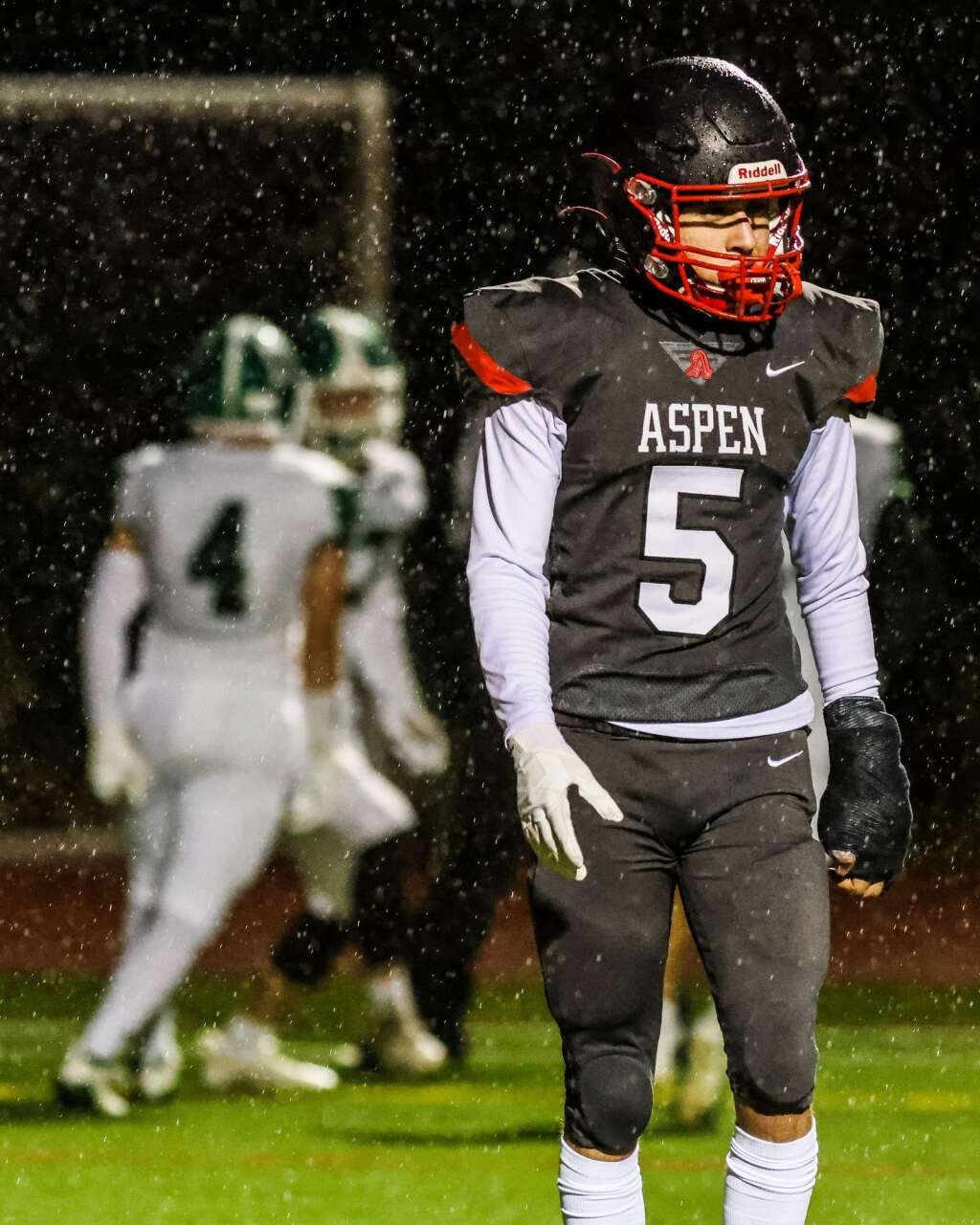 Aspen's Jesus Morales walks away as Delta players celebrate a touchdown on Friday, Oct. 8, 2021, on the AHS turf. Photo by Austin Colbert/The Aspen Times.