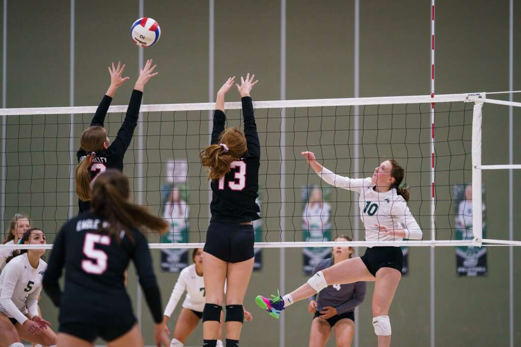 Summit High School sophomore Ella Snyder sends a spiked ball past the jumping Devils' defense during the third set of the Tigers' home conference match loss to the Eagle Valley Devils on Monday, Sept. 20.