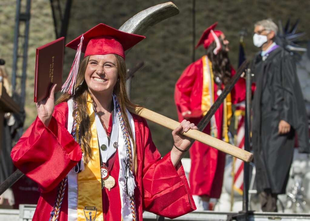 Jillian Perry smiles, waving to friends and family with her diploma and carrying the Mr. Miner mascot's pickaxe during the Park City High School graduation ceremony at the North 40 playing fields Thursday evening, June 3, 2021. Perry was one of nearly 400 graduates that received their diplomas during the ceremony. (Tanzi Propst/Park Record)