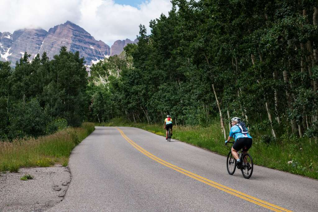 Two e-bikers make their way to the Maroon Bells on Maroon Creek Road in Aspen on Thursday, July 22, 2021. (Kelsey Brunner/The Aspen Times)