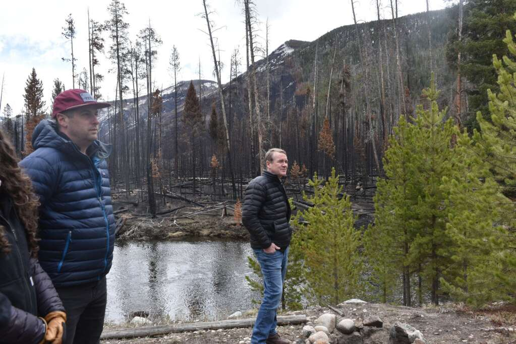 Bennet stands at the Mueller's property line, which borders Rocky Mountain National Park, and hears from local watershed and forest officials about fire recovery efforts. | McKenna Harford/mharford@skyhinews.com