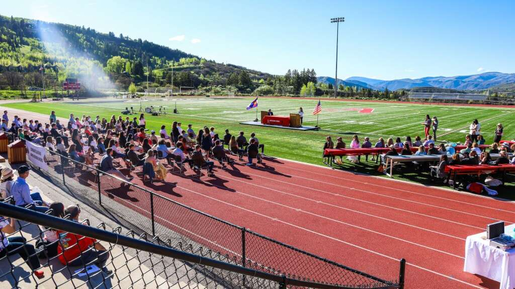 Students await their turn during the Aspen High School senior awards and local scholarship ceremony on Monday, May 24, 2021, on the AHS turf field. Photo by Austin Colbert/The Aspen Times.