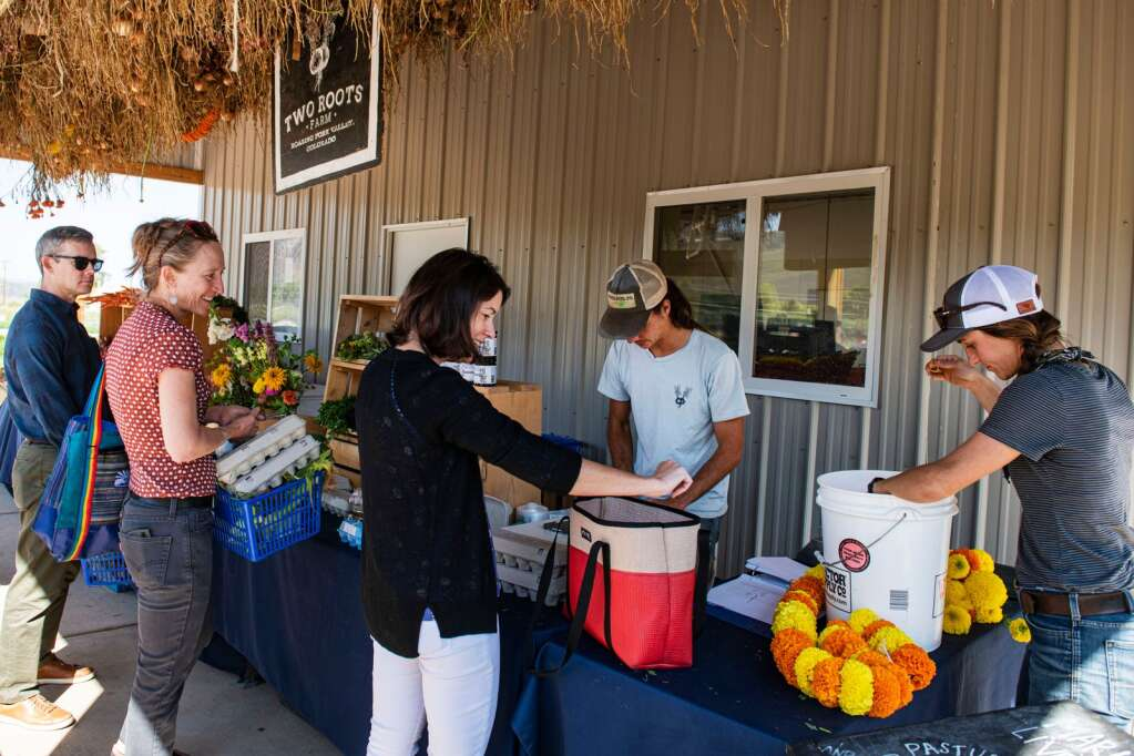 People shop the fresh flowers and produce at the farm stand at Two Roots Farm in Emma on Friday, Sept. 17, 2021. (Kelsey Brunner/The Aspen Times)