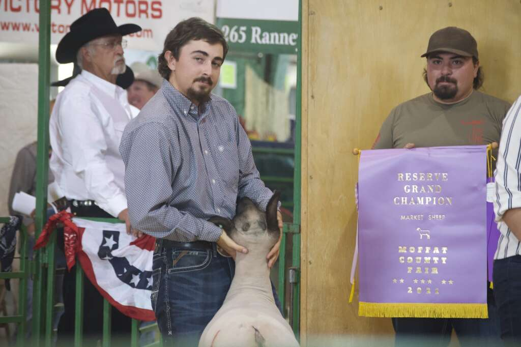 Dustin McLaughlin shows off his reserve champion lamb at the Moffat County Fair livestock auction Saturday evening. | Cuyler Meade / Craig Press
