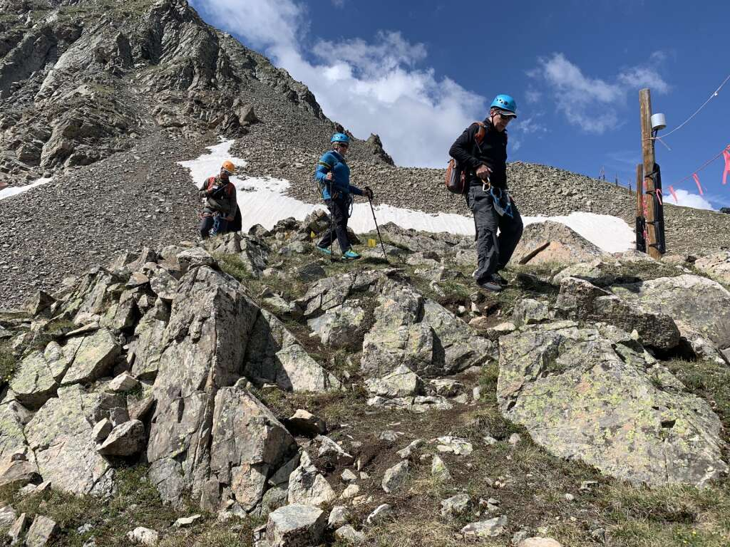 Arapahoe Basin Ski Area via ferrata guests Steve and Anna Clendenen, right, and A-Basin guide Benjamin Zagrzebski, left, hike through talus fields to the base of the via ferrata climb on the East Wall on Tuesday, June 29.   Photo by Antonio Olivero / aolivero@summitdaily.com