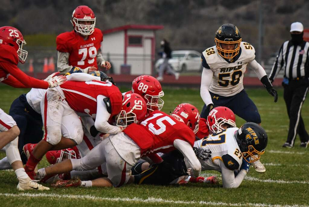 Rifle Bear Embrey Marantino is brought down by a mass of Glenwood Springs Demons during Friday night's rivalry game at Stubler Memorial Field. |Chelsea Self / Post Independent