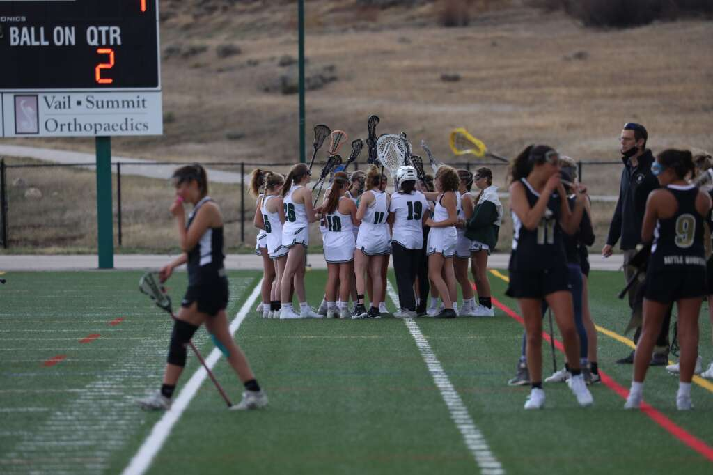 The Summit High School girls varsity lacrosse team huddles in the season opener vs. Battle Mountain on May 8 in Breckenridge. | Photo by Ashley Low / Ashley Low Photography