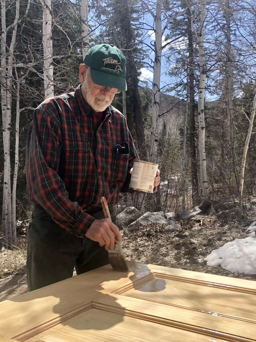 Craton Burkholder stains a wooden door outside the main lodge at the Aspen Camp for the Deaf and Hard of Hearing in Old Snowmass on April 11, 2021. | Kaya Williams/The Aspen Times