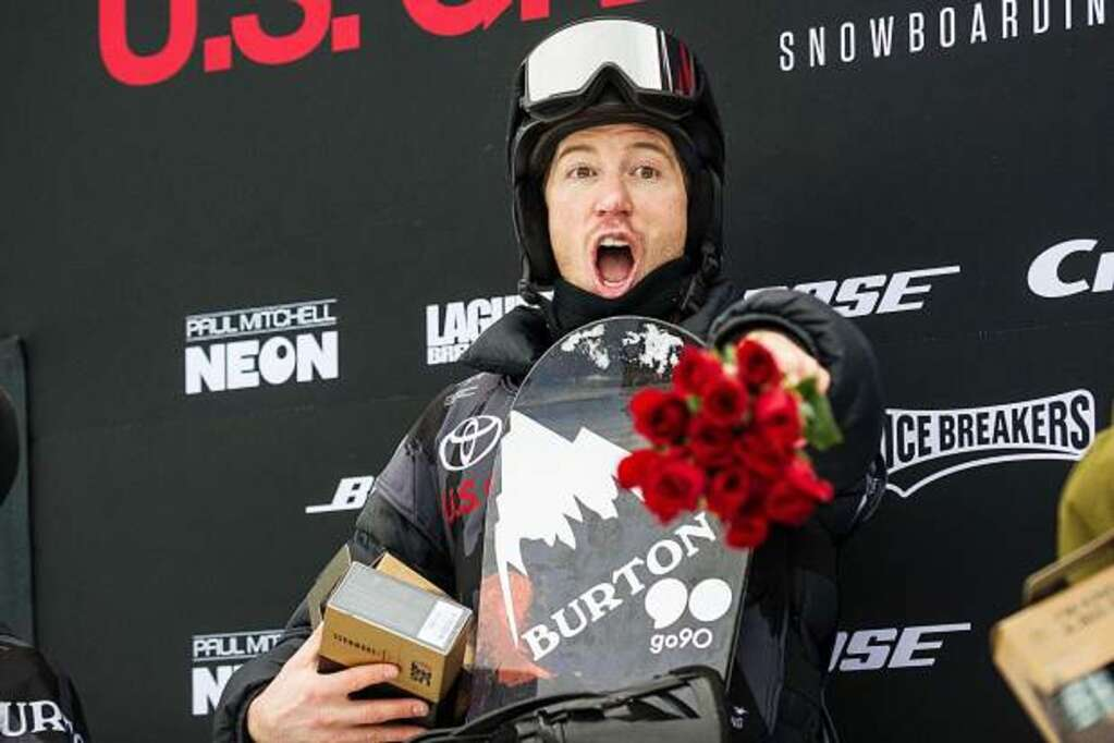Shaun White celebrates on the podium after the men's snowboard superpipe finals Saturday at Snowmass. White earned a100-point score at the Toyota U.S. Grand Prix. He secured his fourth trip to the Olympics.