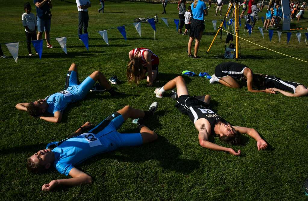 Cross country runners fall to the ground in exhaustion after finishing their race at the Coal Ridge cross country meet at VIX Park in New Castle on Friday morning. |Chelsea Self / Post Independent