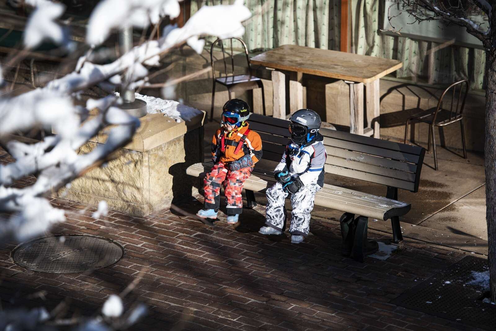 Two children wait on a bench near the line for the ticket office at Aspen Mountain on opening day on Wednesday, Nov. 25, 2020. (Kelsey Brunner/The Aspen Times)