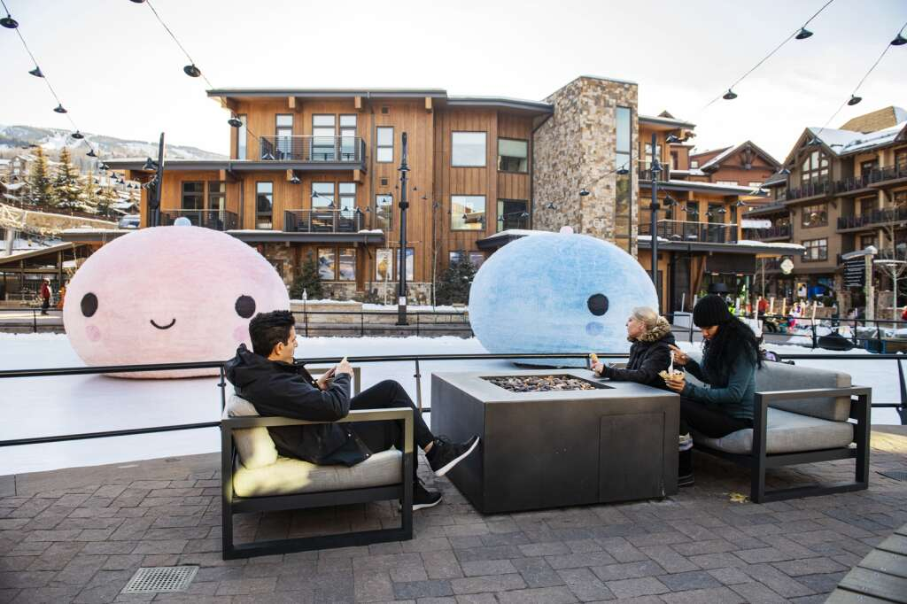 People eat ice cream during a FriendsWithYou Art in Unexpected Places installation event in the rink in Snowmass Base Village on Wednesday, Jan. 6, 2021. (Kelsey Brunner/The Aspen Times)