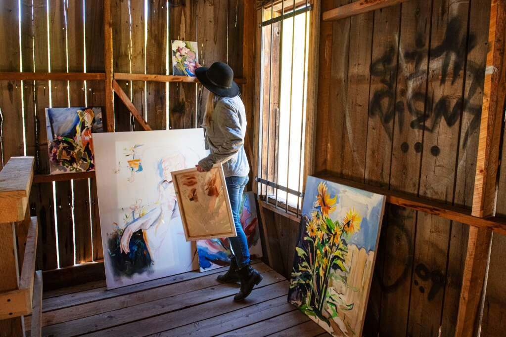 Denver-based artist Kaitlyn Tucek curates a selection of paintings on the wall of a building in the Ashcroft Ghost Town outside of Aspen as part of her two-day exhibition 'The Lilac Hour' outside of Aspen on Friday, Sept. 17, 2021. (Kelsey Brunner/The Aspen Times)