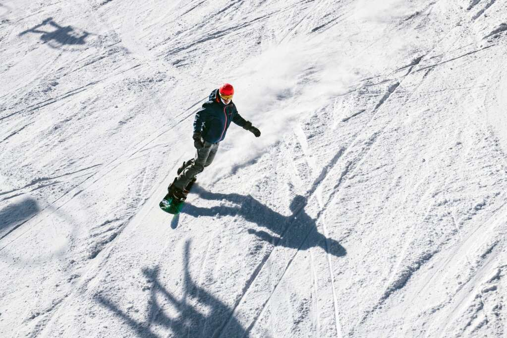 A snowboarder rides under the Ajax Express lift on Aspen Mountain on Thursday, Feb. 18, 2021. All mountains began extended lift operating hours, with select lifts running until 4 or 4:15pm, starting February 13. (Kelsey Brunner/The Aspen Times)